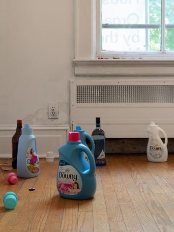 A close-up photograph of detergent bottles and liquor bottles on the ground in front of a window