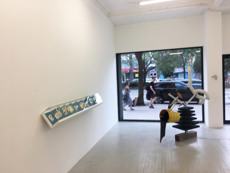 a photograph of the gallery with a sculpture on the ground and a leporello installed on the wall