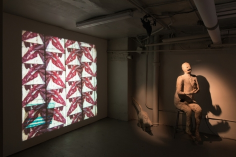 A photograph of the basement of the gallery with a film being projected upon the left wall. At right is a bronze sculpture sitting on a chair.