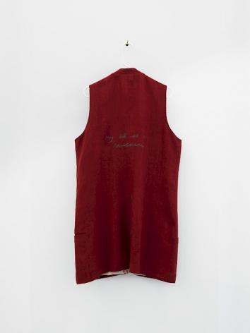 The backside of a cotton, sleeveless knee-length garment, in crimson.