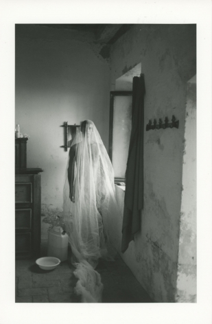 A black and white photograph of a naked man cloaked in a sheer fabric, standing in a room with minimal furniture, stone walls.