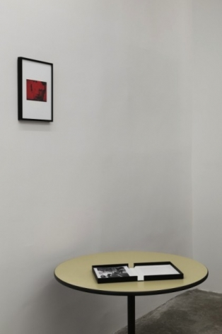 A photograph of a book on a table with a framed red photograph above it.
