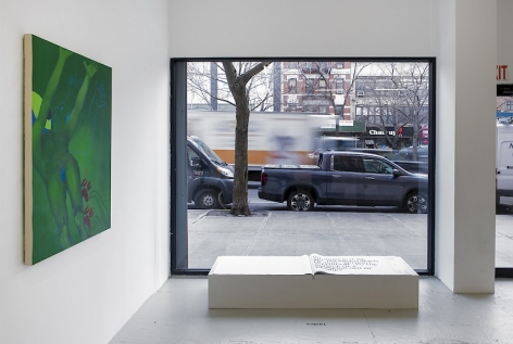 An installation view of Ranee Henderson's green painting and Shawné Michaelain Holloway's book in front of the gallery's main window