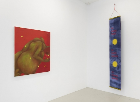 An installation view of a red painting by Ranee Henderson and Crystal Z. Campbell's textile banner