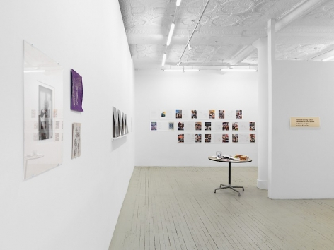A photograph of the long line down the length of the gallery. The artwork on the back wall of magazine spreads is visible alongside a table in the middle of the room At left is a single photograph by Guibert and 2 drawings by Ettinger.