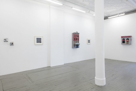 A photograph of the gallery interior, with 2 small sculptures at left installed on the wall. These works are followed by a black and white drawing, then a building facade sculpture, then another drawing that is illegible, then another facade sculpture on the opposite wall in the background.