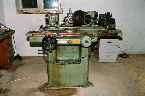 A photograph of a factory grinder machine, sea-foam green, stationed in a desolate room with grey walls and one window