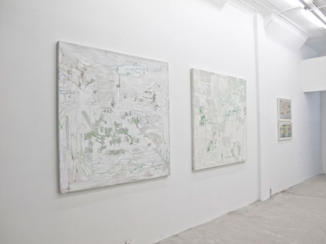 A photograph of 2 abstract square paintings, and a set of 2 drawings, framed, beyond them on the same wall