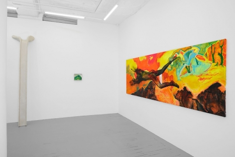 A photograph of the back quadrant of the gallery. There is a large, horizontal, brightly colored painting at right, taking up almost the entire wall. On the left there's a sculpture that leans on the wall, and a small painting to the right of it that is mostly green.