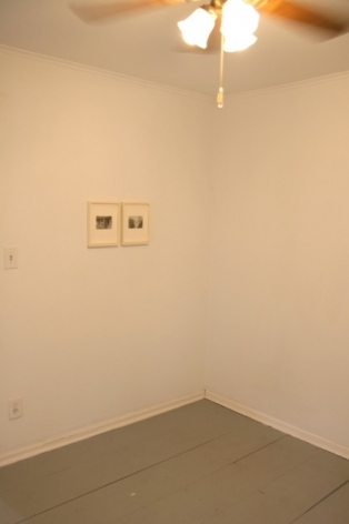 A photograph from inside a small room with 2 framed works at left