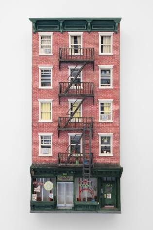 A facade of a building made out of foam and paper. There is a fire escape that runs centrally up the building, and 4 rows of 3 windows. On the ground floor is a bar. The artwork is hung on the wall.