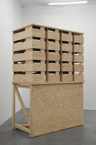 A photograph of a natural wood structure that contains 20 plywood crates to hold envelope boxes and correspondence. The structure resembles a DJ stand at the bottom (one slate of wood with a shelf).