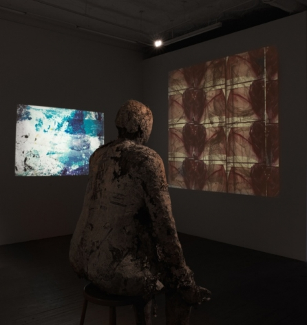 A photograph of the back half of the gallery: we are standing behind the bronze figural sculpture in the middle of the room and there are 2 videos being screened on the 2 walls at right of the gallery's entrance. The video on the left has white and blue imagery upon it; the video to the right has red and brown images upon it.