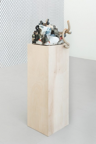 A ceramic sculpture on a raw wood pedestal, with the chainlink fence wallpaper in the background.
