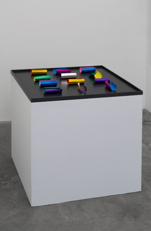 A photograph of a black stage upon a white pedestal. Upon the white stage, which has a depth of about 3 inches, are 12 pieces of square colored papers in various hues. They are partially curled, each one individiated.