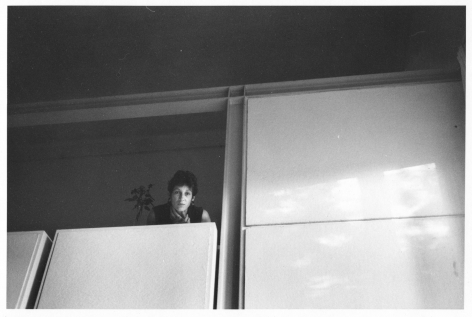 A black and white photograph of Christine Guibert. She is dressed and looking at the camera. She is wedged above a grouping of cabinets: to her right are 2 white rectangles, and below her are 2 more sets of cabinets. She is looking at the camera, and has short dark hair.
