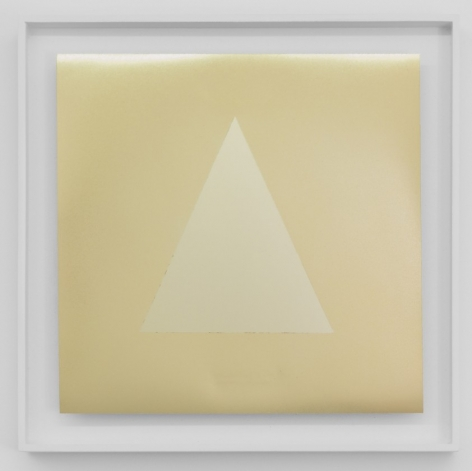 A square artwork that has a triangle centrally situated on a gold ground. All surfaces are highly reflective. The work is framed in white.