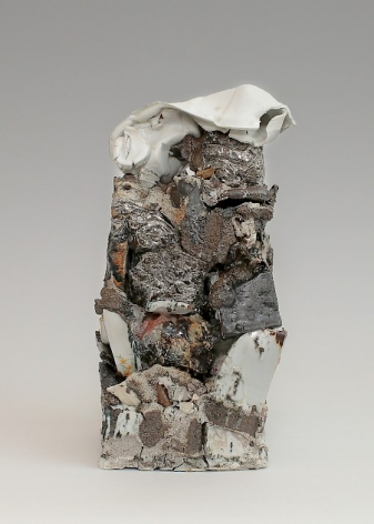 A sculpture of stacked stoneware. Several areas have a shiny silver luster. At the top is a folded piece of white ceramic that resembles a melted plastic bottle. There is a mixture of textures (gravel, sand, smooth stone) that resemble the environment despite being made entirely from clay.