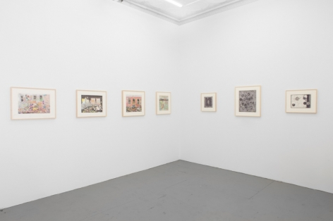 A photograph of the back office of the gallery and a single row of drawings about the corner. On the left wall are 4 color drawings, on the right are 3 black and white drawings. All the drawings are framed in natural wood.