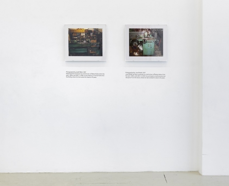 An installation view of 2 photographs by Jiri Skala of factory machines