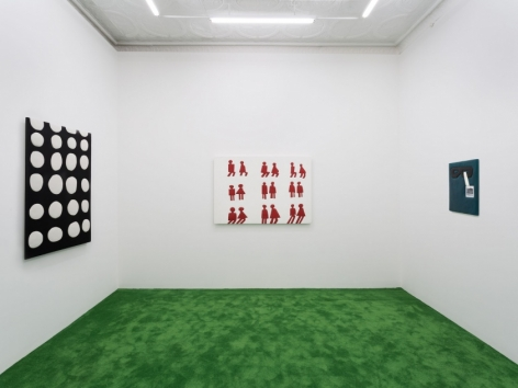 A view of the back room of the gallery. There is one work on each of the three walls: the black-and-white polka dot work at left; a white surface with 9 pairs of figures found on bathroom signs; and a smaller work at right.