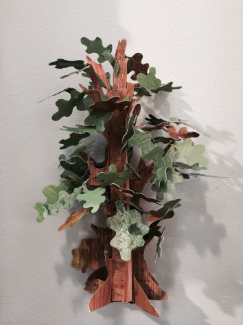 A photograph of an oak tree made from paper. It is three-dimensional with green leaves in varied patterns. The sculpture is hung on the wall, but can be stood up.