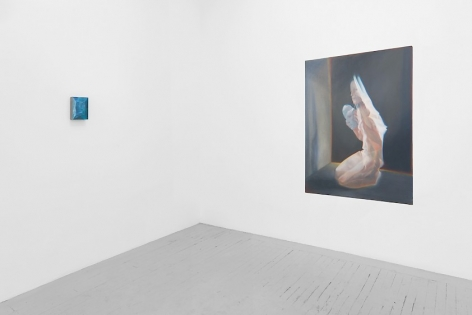A view of 2 artworks around the corner of the gallery. On the left is a small abstract painting in blue tones; on the right is a kneeling naked woman seemingly made of cellophane, holding a mask of a human face. We see her shadow on the wall she's facing, with a black wall behind her, outlined in a warm yellow hue.