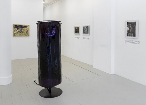 An installation view of Ajay Kurian's vinyl shower-curtain sculpture, 3 photographs by Jiri Skala of factory machines, and one painting by Crystal Z. Campbell