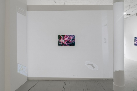 The backside of the temporary wall in the gallery which includes a single artwork and a video being played over it. The video itself is a Google image of the interior of the gallery, which also has the artwork embedded. We see another work at right, on a far wall near the entrance of the gallery.