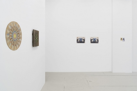 An installation view of 2 mandala works at left (cardboard, wood board) with 2 more works on the far wall. The far wall has 2 photographs, and one small drawing.