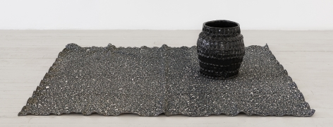 a black glazed vessel upon a woven rug