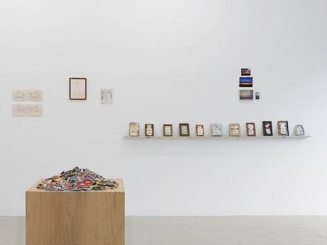 An installation view with a pedestal filled with magazine clippings in the foreground at left. On the wall in the distance is a sculpture made up of old cigarette cartons on a shelf, and 2 other drawings on paper without frames.