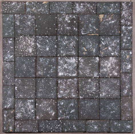 A square sculpture made up of 45 black clay tiles, here seen from above, with specks of white clay scattered throughout.