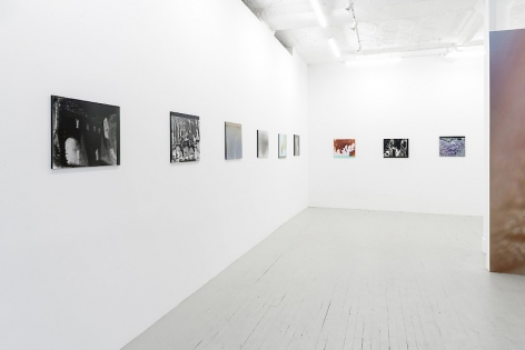 A partial view of the entire gallery. 6 color photographs on plexiglass are on the wall at left, 3 works on the back wall. At right we see an excerpt of the wallpaper created by the artist.