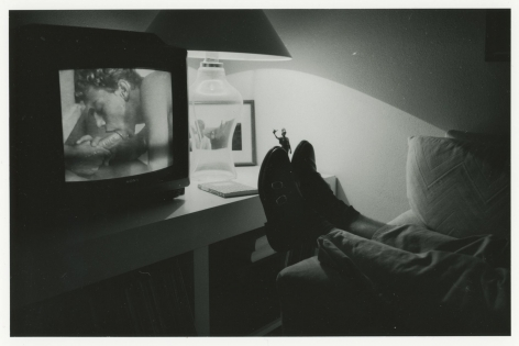 A black and white photograph of a television at the left, hosting a pornographic image of an erect penis in a man's mouth. To the right of the TV on a table is a glass lamp. In the foreground are two black shoes propped on the arm of a couch, with 2 legs leading off in the bottom-right corner.