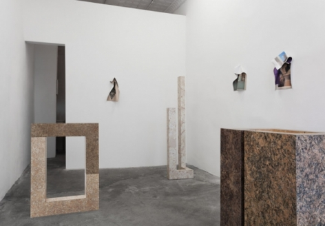 A photograph of the back half of the gallery with 3 sculptures on the ground, and 3 photographic works on the wall