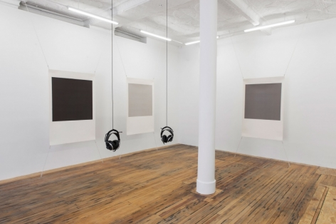 A photograph of the back corner of the gallery, where 3 screenprint works by Bergvall are stretched at all 4 of their corners. In the center of the room are 2 hanging sets of headphones.