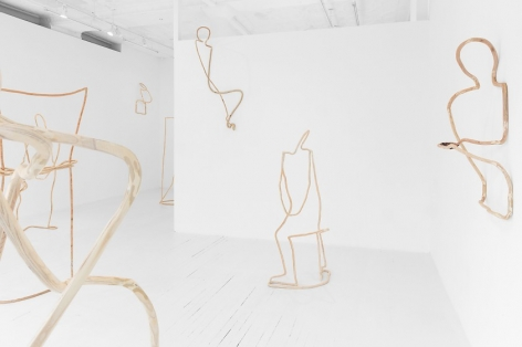An installation photograph of 3 sculptures made of plywood hung on the walls (at right, in center middle-ground, at left in background). There are also 5 sculptures visible on the floor, but several are excerpted and out of the frame of the photo.