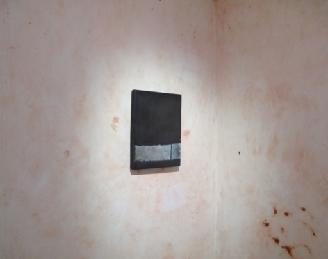 A photograph of one black and gray painting on a wall painted over with splotchy pink