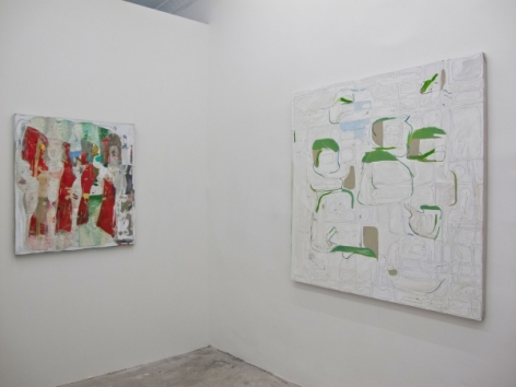 A photograph of 2 abstract paintings on 2 walls, around a corner