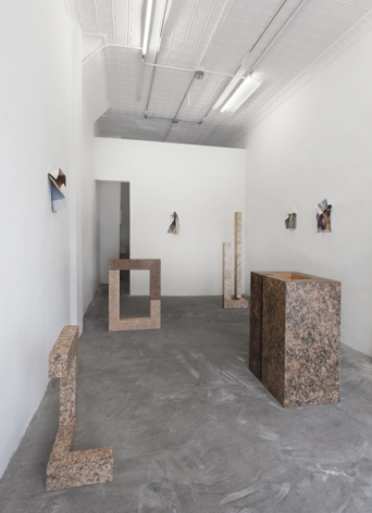 A photograph of the gallery with 4 sculptures on the ground and 4 photo works installed upon 3 different walls