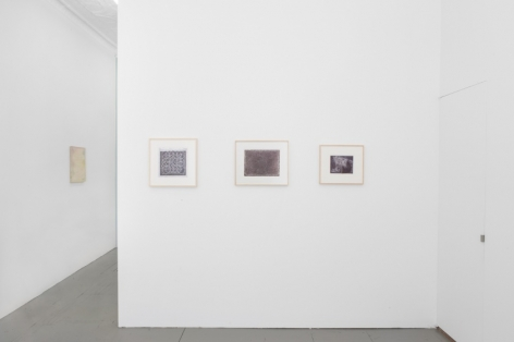 A photograph of the partial wall in the back office of the gallery. There are three black and white drawings on the wall in a single row, framed in natural wood.