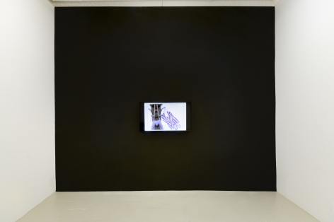 a black wall onto which a flat panel monitor is hanging that is displaying an animated video