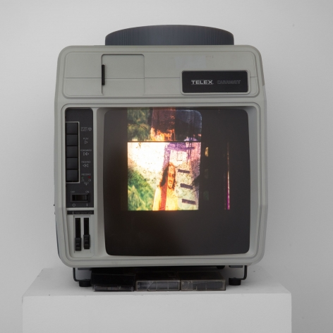 A slide viewer with a single slide carousel, an image is being projected of a long-haired man near a green bush.