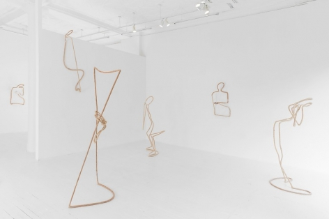 A photograph of 3 sculptures installed on the floor of the gallery, and 3 installed on the walls. The sculptures resemble human bodies.