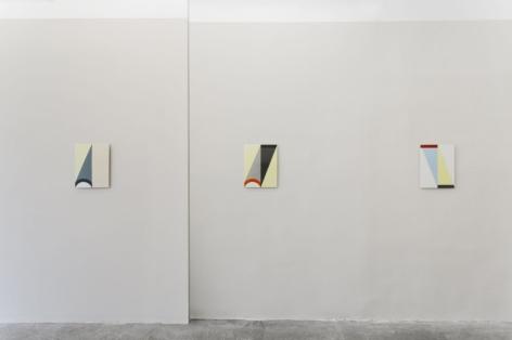 Three enamel paintings hung on a gray wall