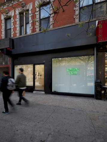 "A photograph of the exterior of the gallery from the sidewalk, where the neon sign ""Green God"" is visible."