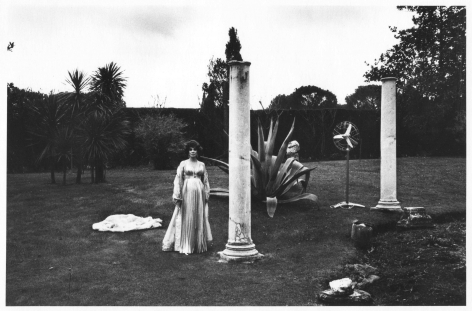 A black and white photograph of Gina Lollobrigida standing in an evening gown outside, next to several Roman columns and large plants. The sky is grey.
