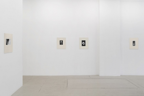 An installation view of 4 black and white Guibert photographs, placed in cream-colored frames made from watercolor paper, hung on the wall
