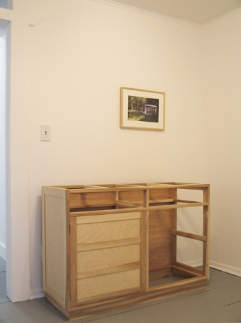 A photograph of a photo, framed, above a deconstructed dresser, some are empty